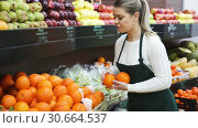 Купить «Young woman selling fresh oranges and fruits on the supermarket», видеоролик № 30664537, снято 12 февраля 2019 г. (c) Яков Филимонов / Фотобанк Лори