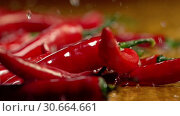 Купить «Slow motion of dropping chili pepper pods under splash spray water», видеоролик № 30664661, снято 26 апреля 2019 г. (c) Gennadiy Poznyakov / Фотобанк Лори