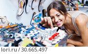 Купить «Portrait of woman looking after pair of shoes for kid», фото № 30665497, снято 24 июня 2019 г. (c) Яков Филимонов / Фотобанк Лори