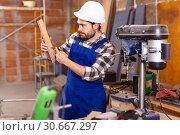 Купить «Portrait of worker who works on drilling machine», фото № 30667297, снято 6 марта 2019 г. (c) Яков Филимонов / Фотобанк Лори
