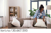 Купить «african american woman arranging sofa cushions», видеоролик № 30667593, снято 15 апреля 2019 г. (c) Syda Productions / Фотобанк Лори