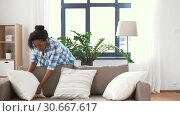 Купить «african american woman arranging sofa cushions», видеоролик № 30667617, снято 15 апреля 2019 г. (c) Syda Productions / Фотобанк Лори