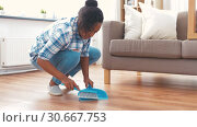 Купить «happy woman with brush and dustpan sweeping floor», видеоролик № 30667753, снято 15 апреля 2019 г. (c) Syda Productions / Фотобанк Лори