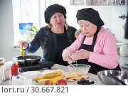 Two old women making pancakes in the kitchen. Стоковое фото, фотограф Константин Шишкин / Фотобанк Лори