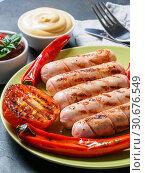 Купить «Grilled chicken sausages close up», фото № 30676549, снято 4 июля 2017 г. (c) Ольга Сергеева / Фотобанк Лори