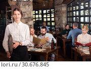 Купить «Waitress welcoming in rustic restaurant», фото № 30676845, снято 11 апреля 2019 г. (c) Яков Филимонов / Фотобанк Лори