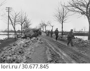 Купить «GERMANY Near Monshau Forest -- 03 Feb 1945 -- American infantrymen of the US Army 2nd Infantry Division, pass bodies of dead Germans and knocked-out equipment...», фото № 30677845, снято 23 мая 2012 г. (c) age Fotostock / Фотобанк Лори