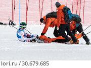 Купить «Спасатели Камчатского спасательного отряда оказывают первую медицинскую помощь горнолыжнику, получившему травму, перед его эвакуацией на спасательных носилках со склона горы во время Чемпионата России по горным лыжам», фото № 30679685, снято 28 марта 2019 г. (c) А. А. Пирагис / Фотобанк Лори