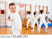 Купить «Sporty young man fencer practicing effective fencing techniques in training room», фото № 30680353, снято 11 июля 2018 г. (c) Яков Филимонов / Фотобанк Лори