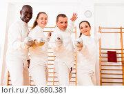Купить «Smiling fencers posing with foils together at fencing room», фото № 30680381, снято 11 июля 2018 г. (c) Яков Филимонов / Фотобанк Лори