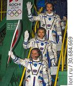 Baikonur Cosmodrome, Kazakhstan. 07 November, 2013. Winter Olympics torch in space.Expedition 38 Soyuz Commander Mikhail Tyurin of Roscosmos, holding the... Редакционное фото, фотограф Jonathan William Mitchell / age Fotostock / Фотобанк Лори