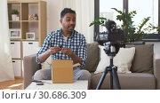 Купить «male blogger taking smartphone out of parcel box», видеоролик № 30686309, снято 26 апреля 2019 г. (c) Syda Productions / Фотобанк Лори