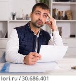 Купить «Distressed male having problems with paying utility bills», фото № 30686401, снято 25 декабря 2017 г. (c) Яков Филимонов / Фотобанк Лори