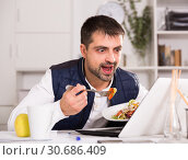 Купить «Portrait of man eating vegetable salad at table with laptop», фото № 30686409, снято 25 декабря 2017 г. (c) Яков Филимонов / Фотобанк Лори