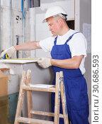 Купить «Contractor installing drywall construction», фото № 30686593, снято 28 мая 2018 г. (c) Яков Филимонов / Фотобанк Лори