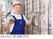 Купить «Construction worker using screw gun for aluminum profile mounting at indoors building site», фото № 30686613, снято 28 мая 2018 г. (c) Яков Филимонов / Фотобанк Лори