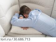 Купить «Depressed teenager lying face down on sofa», фото № 30686713, снято 23 февраля 2019 г. (c) Володина Ольга / Фотобанк Лори