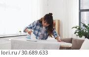 Купить «asian woman ironing bed linen at home», видеоролик № 30689633, снято 25 апреля 2019 г. (c) Syda Productions / Фотобанк Лори