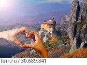 Купить «Hand hold red heart over Monastiraki monastery», фото № 30689841, снято 8 января 2014 г. (c) Сергей Новиков / Фотобанк Лори