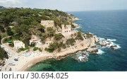 Купить «View from drone of Castell d'en Plaja in Mediterranean coastal town of Lloret de Mar, Catalonia, Spain», видеоролик № 30694025, снято 11 июня 2018 г. (c) Яков Филимонов / Фотобанк Лори