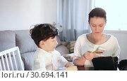 Купить «Smiling woman giving pocket money to her preteen son at home», видеоролик № 30694141, снято 26 апреля 2019 г. (c) Яков Филимонов / Фотобанк Лори