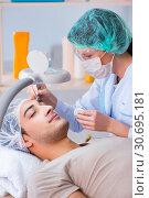 Купить «Young handsome man visiting female doctor cosmetologist», фото № 30695181, снято 16 ноября 2017 г. (c) Elnur / Фотобанк Лори
