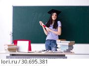 Купить «Female graduate student in front of green board», фото № 30695381, снято 16 января 2019 г. (c) Elnur / Фотобанк Лори