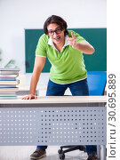 Купить «Young male student in front of green board», фото № 30695889, снято 26 февраля 2019 г. (c) Elnur / Фотобанк Лори