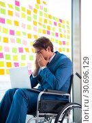 Купить «Young handsome man in wheelchair with many conflicting prioritie», фото № 30696129, снято 25 августа 2018 г. (c) Elnur / Фотобанк Лори