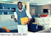 Купить «Young seller who is standing with prices», фото № 30696481, снято 19 февраля 2018 г. (c) Яков Филимонов / Фотобанк Лори
