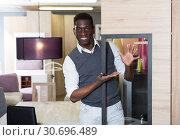 Купить «Portrait of seller man who is offering new furniture», фото № 30696489, снято 19 февраля 2018 г. (c) Яков Филимонов / Фотобанк Лори