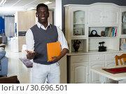 Купить «Assistant male is standing with prices», фото № 30696501, снято 19 февраля 2018 г. (c) Яков Филимонов / Фотобанк Лори