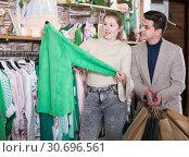 Купить «Smiling woman and man are choosing clothes and looking on green jacket», фото № 30696561, снято 12 марта 2018 г. (c) Яков Филимонов / Фотобанк Лори