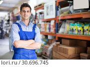 Купить «Portrait of adult male seller in uniform at workplace», фото № 30696745, снято 26 июля 2017 г. (c) Яков Филимонов / Фотобанк Лори