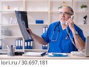 Купить «White bearded old doctor radiologist working in clinic», фото № 30697181, снято 26 декабря 2018 г. (c) Elnur / Фотобанк Лори