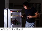 Купить «Man breaking diet at night near fridge», фото № 30698553, снято 8 февраля 2019 г. (c) Elnur / Фотобанк Лори