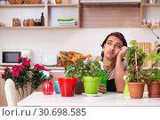 Купить «Young handsome man cultivating flowers at home», фото № 30698585, снято 25 февраля 2019 г. (c) Elnur / Фотобанк Лори