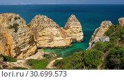 Купить «Pinheiros beach and limestone rocky sea coast near Lagos, Algarve, Portugal», видеоролик № 30699573, снято 21 марта 2019 г. (c) Serg Zastavkin / Фотобанк Лори