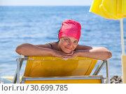 Купить «Молодая женщина загорает на шезлонге возле моря. Смотрит в камеру и улыбается», фото № 30699785, снято 23 июля 2018 г. (c) Кекяляйнен Андрей / Фотобанк Лори
