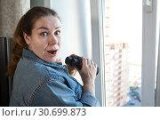 Купить «Потрясенная увиденным взрослая женщина с биноклем у окна», фото № 30699873, снято 16 апреля 2019 г. (c) Кекяляйнен Андрей / Фотобанк Лори