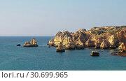 Купить «Small limestone islands near Dona Ana beach and rocky sea coast near Lagos, Algarve, Portugal», видеоролик № 30699965, снято 31 марта 2019 г. (c) Serg Zastavkin / Фотобанк Лори