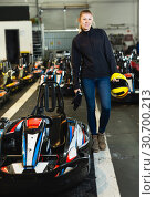 Купить «Female racer holding helmet on kart track», фото № 30700213, снято 18 марта 2019 г. (c) Яков Филимонов / Фотобанк Лори