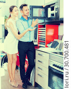 Купить «Young man and woman are choosing new microwave», фото № 30700481, снято 15 июня 2017 г. (c) Яков Филимонов / Фотобанк Лори