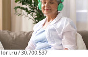 Купить «senior woman in headphones listening to music», видеоролик № 30700537, снято 30 апреля 2019 г. (c) Syda Productions / Фотобанк Лори