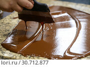 Chocolatier with a spatula is stirring the tempered liquid chocolate on a granite table. Стоковое фото, фотограф Олег Белов / Фотобанк Лори