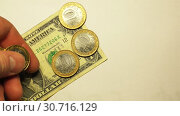 Hand puts six coins of 10 rubles per one US dollar on a white background. Стоковое видео, видеограф Aleksandr Sulimov / Фотобанк Лори