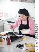 Купить «A grandmother frying pancakes in the home kitchen. Put the dough in the pan», фото № 30718621, снято 13 марта 2019 г. (c) Константин Шишкин / Фотобанк Лори