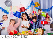 Купить «Boys and girls handing gifts to each other during dinner», фото № 30718821, снято 26 июня 2019 г. (c) Яков Филимонов / Фотобанк Лори
