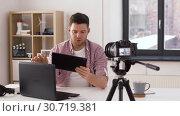 Купить «male blogger with tablet pc videoblogging at home», видеоролик № 30719381, снято 2 мая 2019 г. (c) Syda Productions / Фотобанк Лори