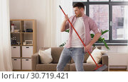 Купить «man with broom having fun and cleaning home», видеоролик № 30719421, снято 2 мая 2019 г. (c) Syda Productions / Фотобанк Лори